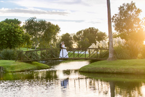 Bride and Groom posing on Bridge on Golf Course during Romantic Photoshoot