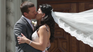 Bride and Groom kiss in front of Cathloic Church after Wedding Ceremony in Los Angeles
